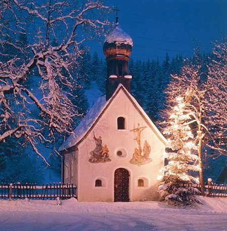 A Christmas tree aglow beside a tiny chapel in Germany's Karwendel mountains.