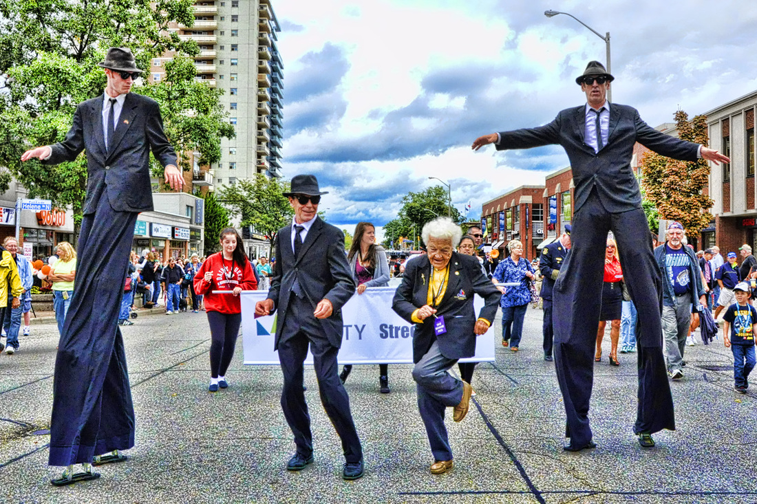 Mayor Hazel McCallion with Top Hat Marching Band and the Stilt Guys at Tim Hortons Southside Shuffle Google image from http://www.southsideshuffle.ca/ticketed-mainstages.html
