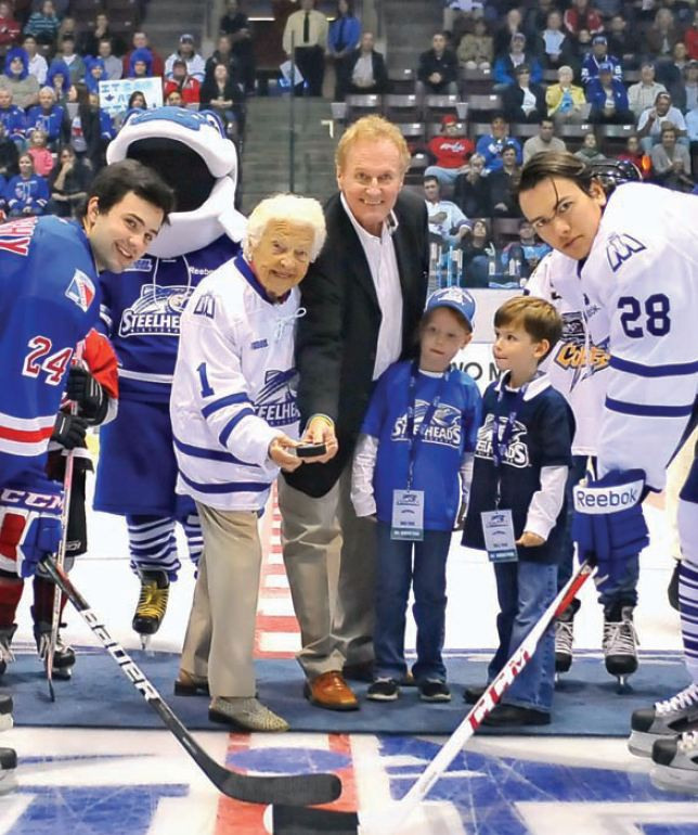 Kitchener Rangers' Ryan Murphy, Mayor Hazel McCallion, Steelheads owner Elliott Kerr, Kerr's son and daughter, and captain Stuart Percy ready to launch the new franchise's first season. Photo by Terry Wilson/OHL Images Google image from http://mississaugalife.ca/wp-content/uploads/2012/11/steelheads-pic.jpg.