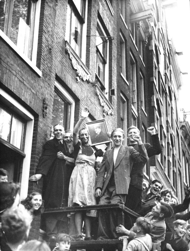 Dutch collaborators with a portrait of Hitler surrounded by 'fans' on the street in Amsterdam, circa 1945 Google image from http://histomil.com/viewtopic.php?f=338&t=3918&start=4140