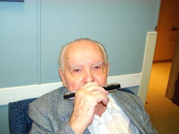 Stanley Filip No. 6, age 94, playing harmonica for fans after performance